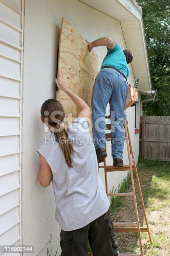 A father and son working together to board up their house for a hurricane.