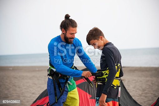 Man and his son holding  kite preparing for kite surfing