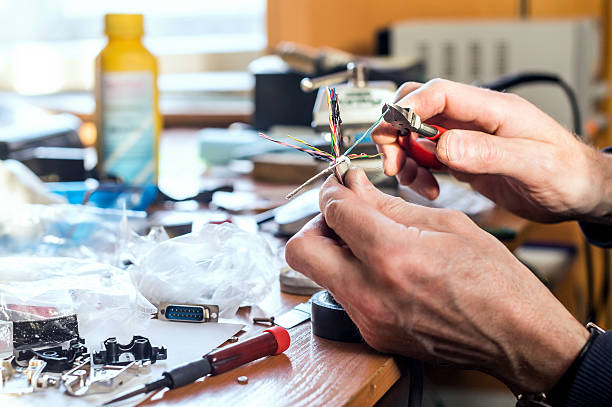 Preparing for soldering by stripping the wire Man's hands holding cable with colorful wires and pliers over the working table in order to strip the wire for soldering. soldering iron stock pictures, royalty-free photos & images