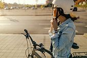 Young woman putting her helmet, preparing for the bike ride