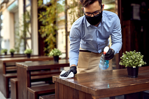 Waiter wearing protective face mask while disinfecting tables at outdoor cafe.