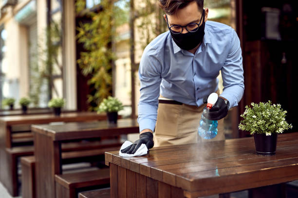Preparing for the customers after reopening! Waiter wearing protective face mask while disinfecting tables at outdoor cafe. restaurants stock pictures, royalty-free photos & images
