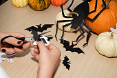 istock Preparing for the Halloween celebration. A girl cuts a bat out of paper. 1279274840