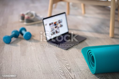 Preparing for training online. Mat, dumbbell, mat and laptop. Preparing for online fitness training at home with laptop and fitness mat. Online training, online fitness, stay home, quarantine, online training.