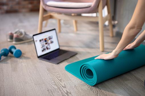Preparing for training online. Mat, dumbbell, mat and laptop.