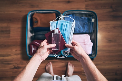 Preparing for travel in new normal. Man packing passport, face masks and hand sanitizer. Themes personal protection and flight rules during coronavirus pandemic.