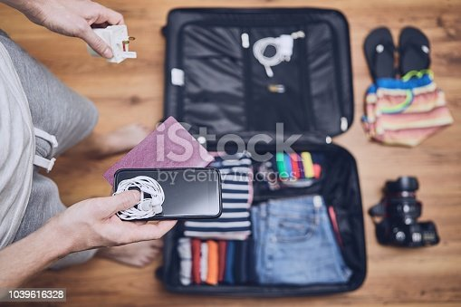 Preparing for trip. Young man packing clothing for vacation, flip flop, camera and other things on hardwood floor.