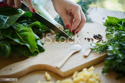 Close up shot of unrecognizable female hand cutting up chard on a cutting board surrounded with abundance of herbs like dill, parsley, basil and leak next to wooden spoons with salt and pepper.