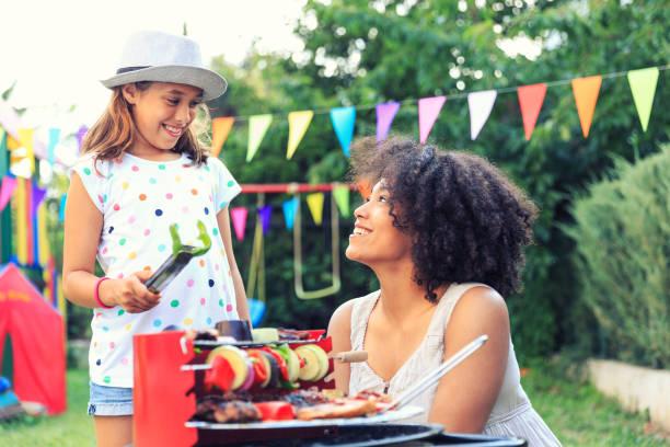 vorbereitung von gegrillten speisen im hinterhof mit tochter - paletten terrasse stock-fotos und bilder