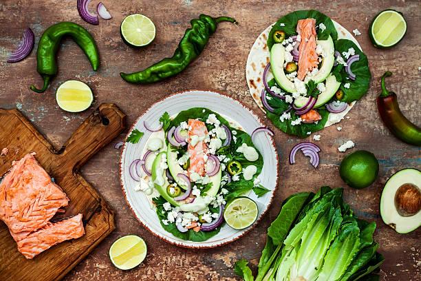 preparing healthy lunch snacks. fish tacos with grilled salmon - meeresfrüchte enchiladas stock-fotos und bilder