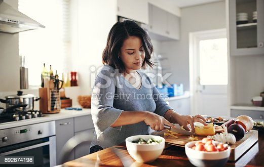 Shot of an attractive young woman cooking at home