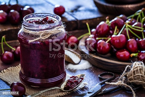 Front view of a glass jar filled with fresh homemade cherry jam shot on dark kitchen table. The jar is at the left of an horizontal frame. Selective focus on foreground. Predominant colors are red and brown. Low key DSRL studio photo taken with Canon EOS 5D Mk II and Canon EF 100mm f/2.8L Macro IS USM.