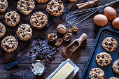 Top view of a rustic wooden table table filled with chocolate chips cookies and ingredients for preparing and baking cookies. Some baked cookies are on a baking sheet, others are on a cooling rack and on a wooden plate. Ingredients includes are flour, eggs, chocolate chips, brown sugar and butter. Some kitchen utensils complete the composition. Predominant color is brown. Low key DSRL studio photo taken with Canon EOS 5D Mk II and Canon EF 100mm f/2.8L Macro IS USM