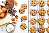 An overhead photo of chocolate chips cookies with a slice of chocolate, shot from above on a piece of baking paper, with copy space