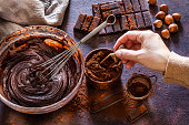 High angle view of a mixing bowl filled with melting chocolate dough shot on dark brown rustic kitchen table. A wire whisk is inside the mixing bowl. A female hand holding a wooden serving scoop is picking a cocoa powder from a small brown bowl. Some chocolate bar pieces are at the top right of an horizontal frame as well as some hazelnuts. A brown bowl with cocoa powder is beside the mixing bowl. Predominant color is brown. Low key DSRL studio photo taken with Canon EOS 5D Mk II and Canon EF 100mm f/2.8L Macro IS USM.