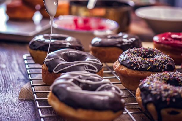 vorbereitung selbstgemachte donuts mit schokolade - deutscher schokoladen zuckerguss stock-fotos und bilder