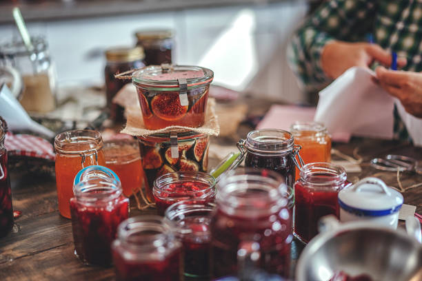 preparing homemade strawberry, blueberry and raspberry jam and canning in jars - marmellata foto e immagini stock