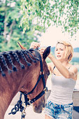 Woman preparing her horse before riding.