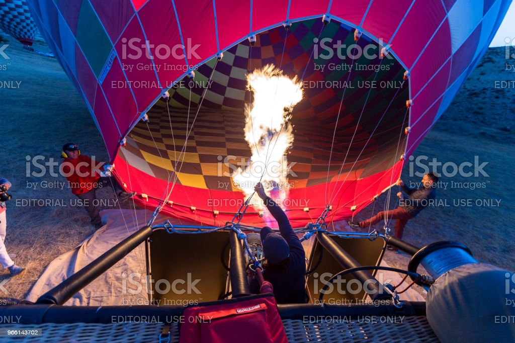 Preparing hot air balloon to flying over the valley at Cappadocia,Anatolia,Turkey.Cappadocia is great tourist attraction place to fly with hot air balloons.NEVSEHIR/TURKEY- JULY 23,2016 - Стоковые фото UNESCO роялти-фри