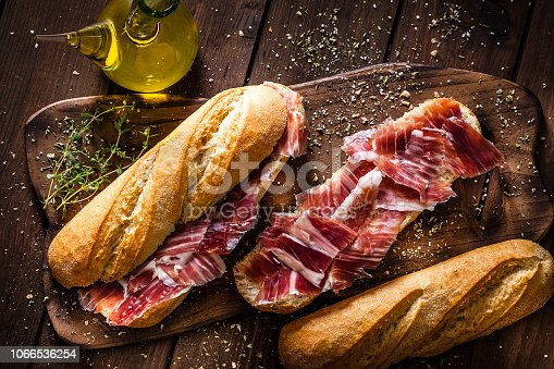 Typical spanish food concepts: High angle view of a rustic wooden table with two delicious Iberico ham sandwich also called in Spain as Bocadillo de Jamón Iberico. Predominant color is brown. Low key DSRL studio photo taken with Canon EOS 5D Mk II and Canon EF 100mm f/2.8L Macro IS USM.