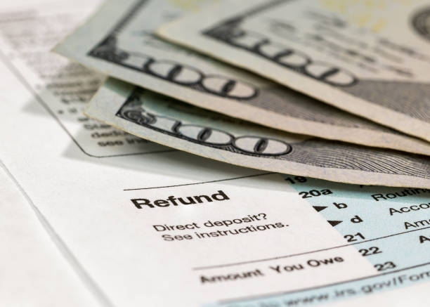 Preparing income tax return Income tax return form ready to be filled out with money in background taxes stock pictures, royalty-free photos & images