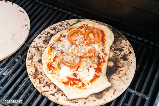 Preparing individual grilled pizzas on an outdoor gas grill.