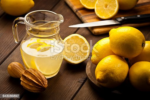 Horizontal shot of a jug with infused lemon water and fresh organic lemons on rustic wood table. A wooden citrus squeezer is beside the jug, one lemon is cut in halves. Predominant colors are yellow and brown. Low key DSRL studio photo taken with Canon EOS 5D Mk II and Canon EF 70-200mm f/2.8L IS II USM Telephoto Zoom Lens