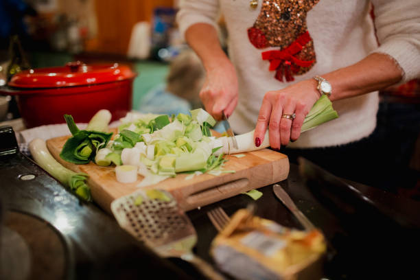 Preparing Leeks for Christmas Dinner Close up shot of a woman chopping up leeks while preparing a christmas dinner at home. leek stock pictures, royalty-free photos & images
