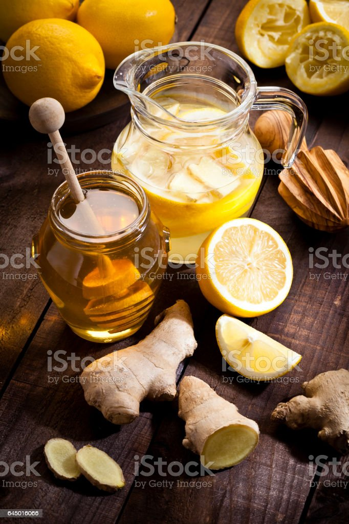 Preparing lemon infused water with honey and ginger stock photo