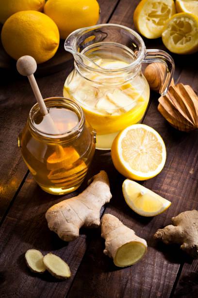 wasser mit honig und ingwer infundiert zitrone vorbereiten - ingwerwasser zubereiten stock-fotos und bilder