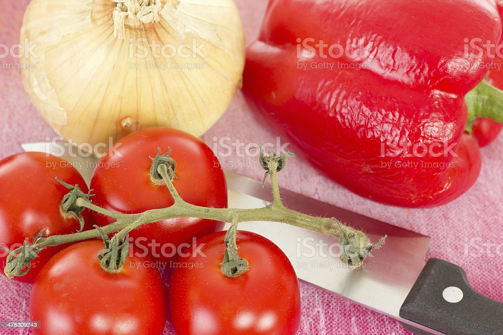 Preparing lunch with red peppers onions and tomatoes royalty-free stock photo