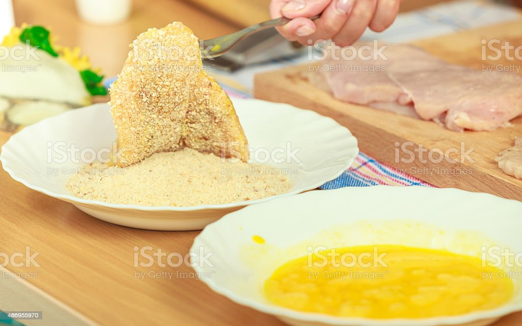 Preparing meal of breaded chicken cutlets stock photo