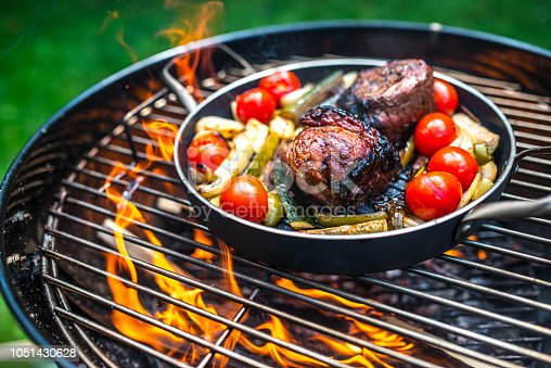 Preparing Meat With Vegetables in Frying Pan on Barbecue Grill.
