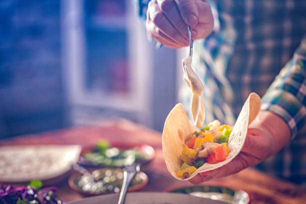 Preparing Mexican Tacos with Spicy Salsa and Shrimps Preparing Mexican Tacos with Spicy Salsa and Shrimps. sour cream stock pictures, royalty-free photos & images