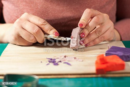 Close-up on young woman hands cutting and cleaning polymer clay. Process of making polymer clay jewelry.