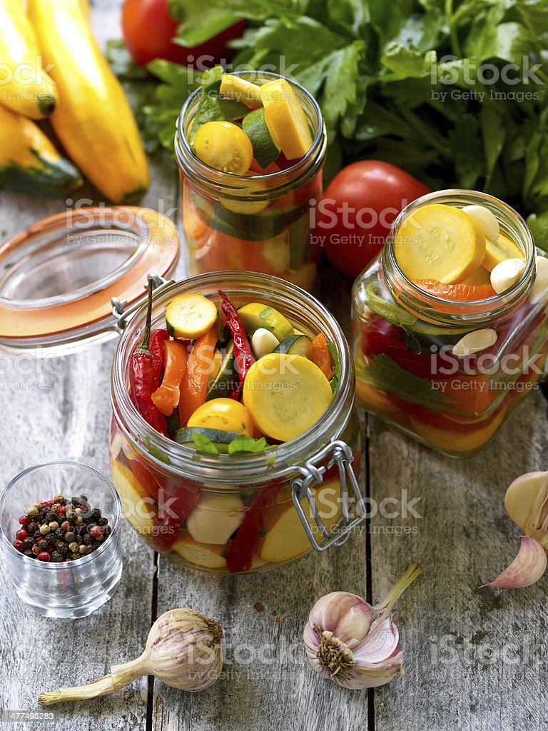 Preparing preserves of pickled zucchini in jars with spices, gar stock photo