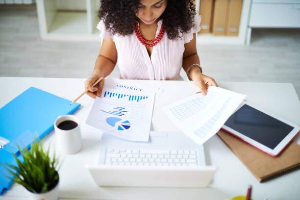 Preparing project report Businesswoman examining documents sitting at office table financial report stock pictures, royalty-free photos & images