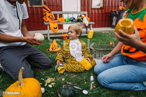 Photo of costumed family, preparing pumpkins for Halloween