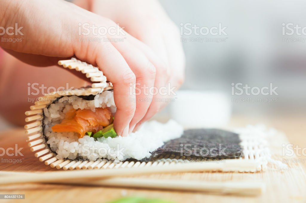 Preparing, rolling sushi. Salmon, avocado, rice and chopsticks on wooden table. stock photo