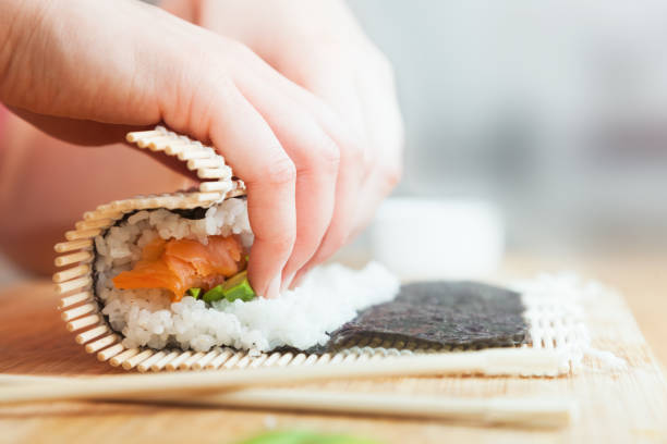 preparing, rolling sushi. salmon, avocado, rice and chopsticks on wooden table. - making stock pictures, royalty-free photos & images