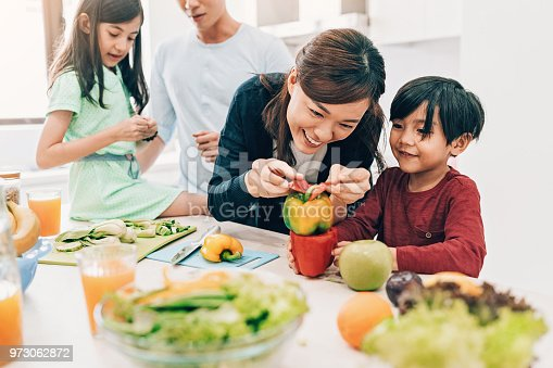 Asian ethnicity family preparing salad together