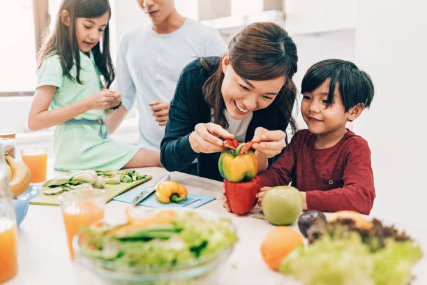 Preparing salad with kids is fun stock photo