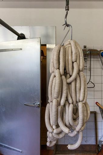 hanging fresh sausages, bratwurst, on rack in workshop. Ready to get smoked