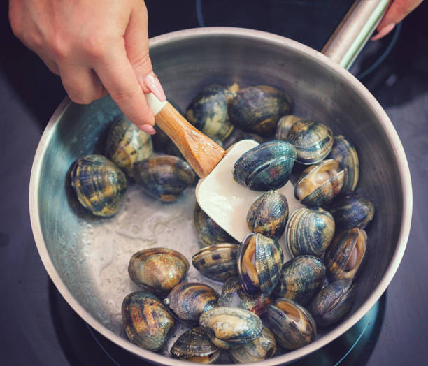 Preparing Spaghetti With Vongole Young women preparing spaghetti alle Vongole at home mollusk stock pictures, royalty-free photos & images