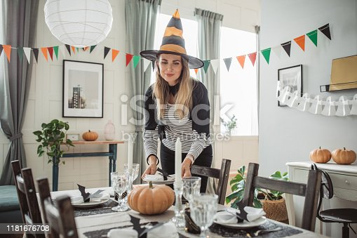 Mature woman in costume setting table for Halloween lunch