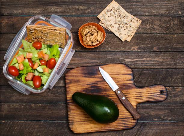 Zubereitung für Kinder zum mitnehmen. Schule-Lunch-Box mit Salat, Lachs, Avocado und Nüssen auf rustikalen hölzernen Hintergrund. Gesunde Ernährung Gewohnheiten Konzept. – Foto