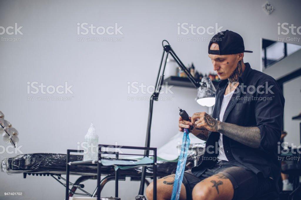 Preparing tattoo machine for work stock photo