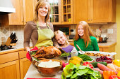 A family of mother and two daughter preparing Thanksgiving dinner with Turkey and all the accompaniments in a home kitchen.