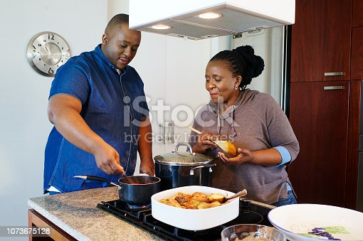 A male and senior lady standing at a gas stove in a kitchen looking in a pot full of tomato sauce Strand Cape Town South Africa