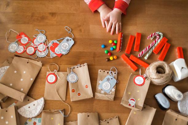 vorbereitung des adventskalenders. taschen und süßigkeiten auf dem tisch. kleine baby-arme für die süßigkeiten zu erreichen - basteln mit kindern weihnachten stock-fotos und bilder